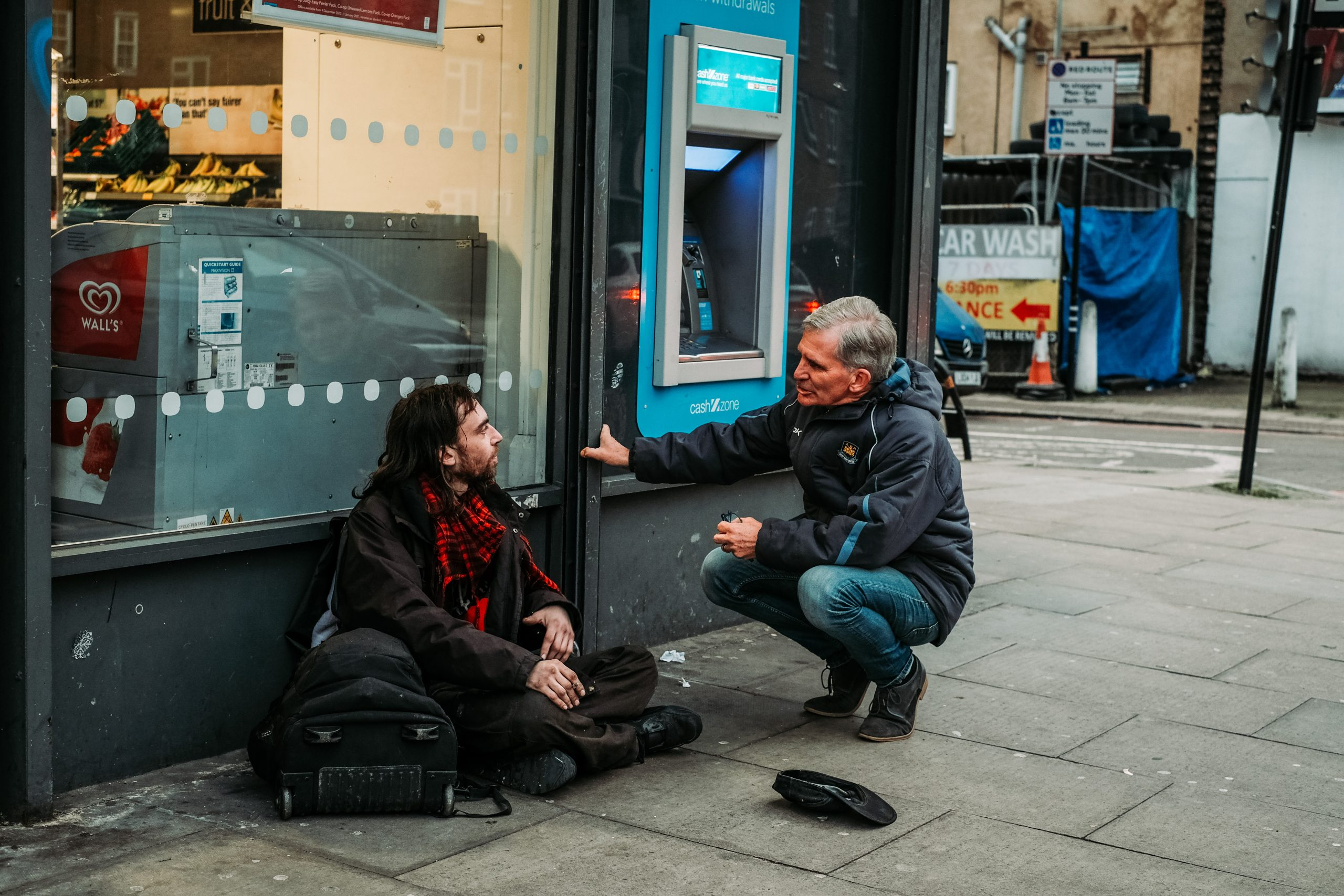 Stephen talking to a homeless man sitting on a street next to a cash point