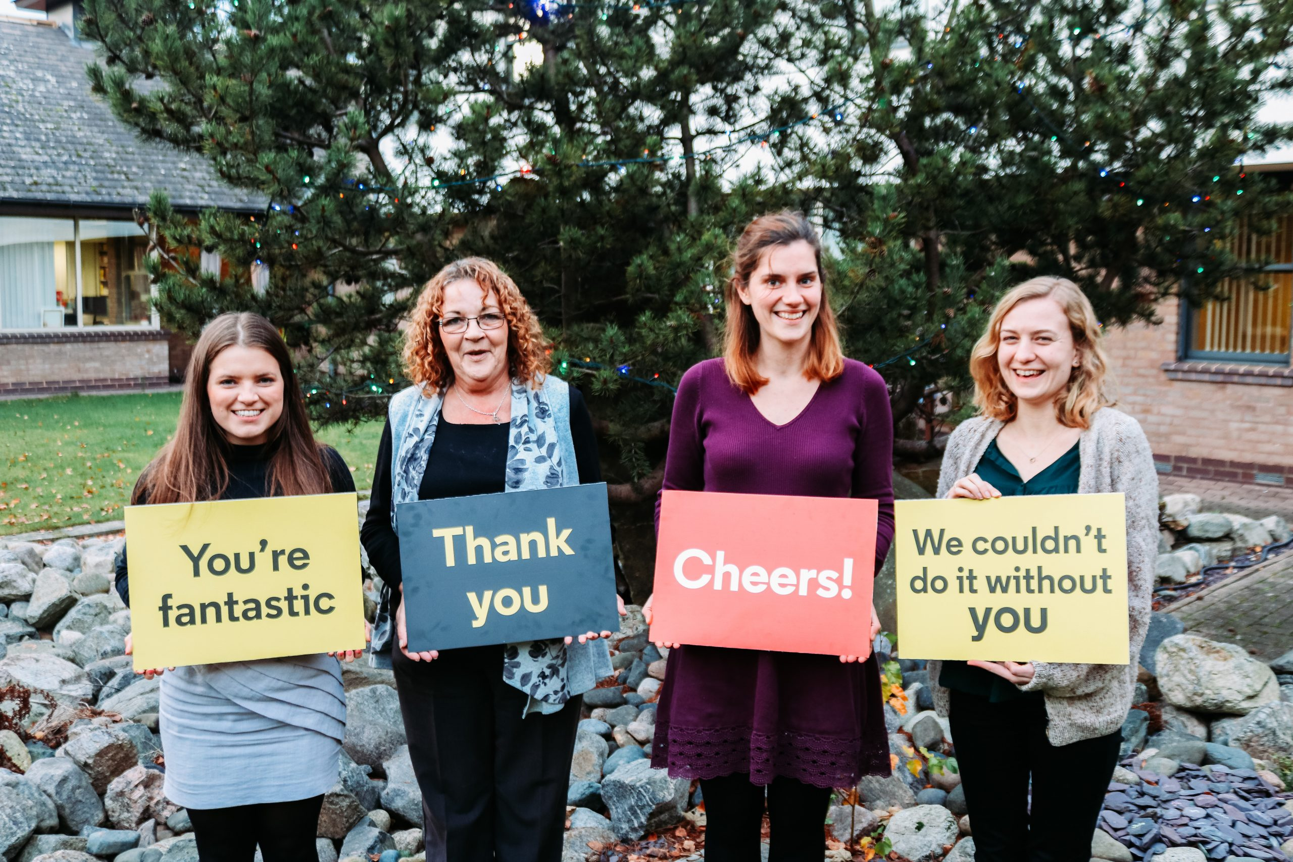 Four staff holding boards saying thank you