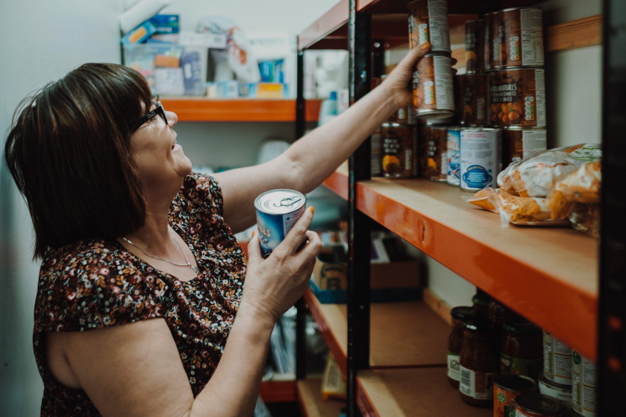 Jane putting tins on a food bank shelf